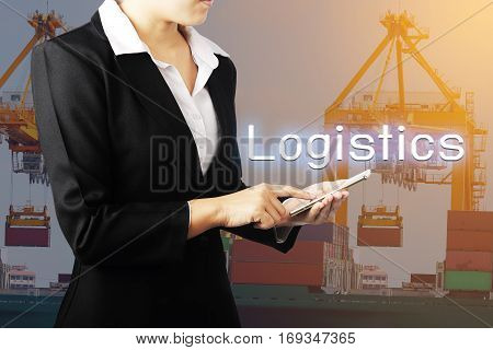 Businesswoman holding phone over container cargo freight ship with working crane bridge in shipyard background.