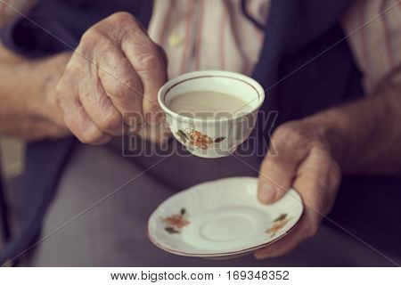 Detail of an elderly woman's hands holding a rustic cup filled with coffee with cream