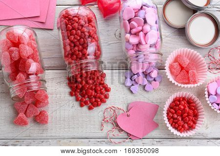 High angle view of different Valentines Day Candies on a rustic white wood table. Canning jars on their sides with candy spilling out.