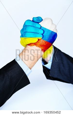 Governments conflict concept. Male hands colored in Ukrainian and Russian flags arm wrestling on light background