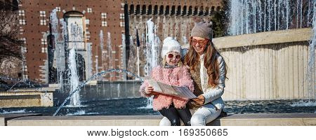 Rediscovering things everybody love in Milan. Full length portrait of smiling modern mother and child tourists in sunglasses near Sforza Castle in Milan Italy looking at the map