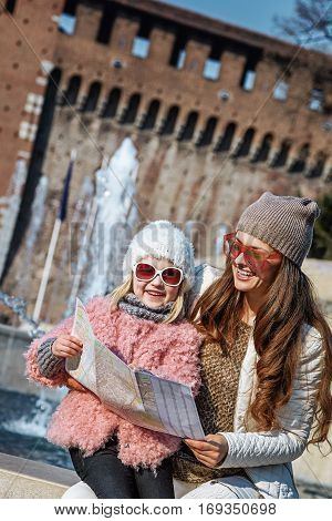 Rediscovering things everybody love in Milan. happy modern mother and daughter tourists in sunglasses in Milan Italy with map