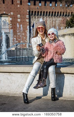 Mother And Daughter Travellers Taking Photo With Digital Camera