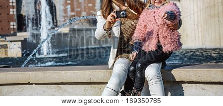 Rediscovering things everybody love in Milan. modern mother and daughter travellers in Milan Italy with digital camera taking photo