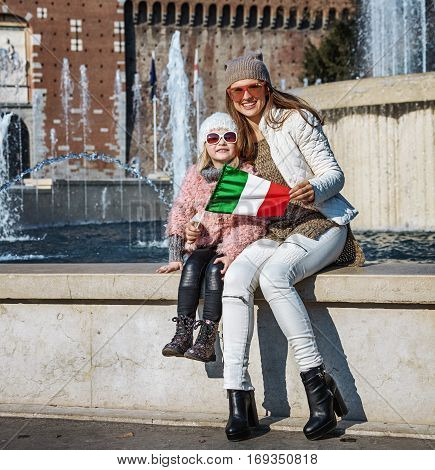 Smiling Mother And Child Tourists In Milan, Italy Showing Flag
