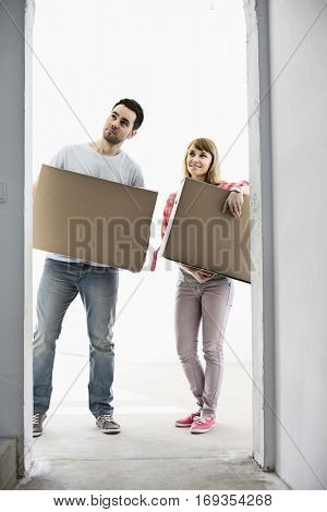 Full-length of couple with cardboard boxes standing in front of entrance