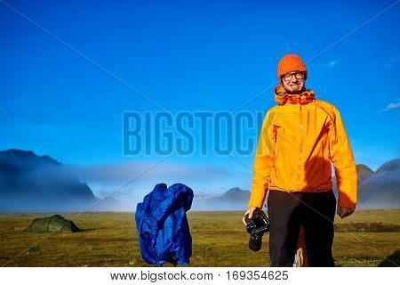 man hiker photographer taking picture on the mountain lake background in Iceland