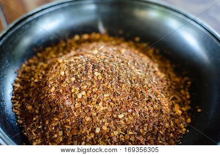 Close up Homemade Chili Powder or Cayenne Pepper in the Black Pan. Spicy Herb Good for Healthy Favorite to use in Asia.
