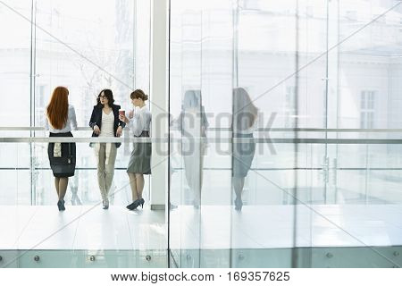 Businesswomen conversing at office hallway