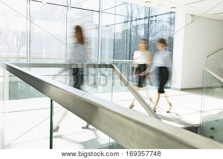 Blurred motion of businesswomen walking at office hallway