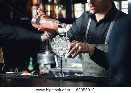 Closeup Of Bartender Hands Pouring Alcoholic Drink Into A Jigger To Prepare A Cocktail, With Red Bel