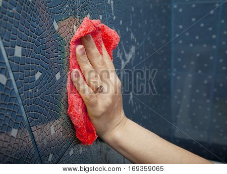 female hand washing red tile on the wall with a cloth lather in the bathroom