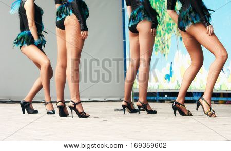 legs of four girls dancing on stage outside closeup