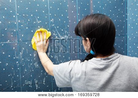 woman in a gray shirt washing blue tile with a cloth with soapy foam in the bathroom