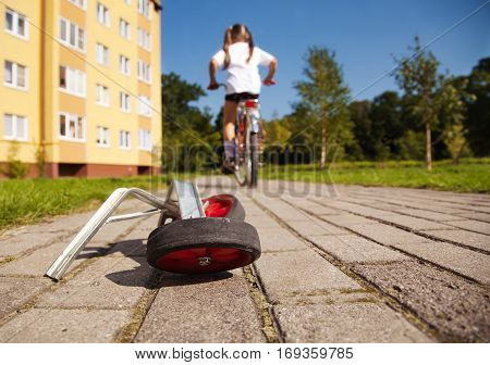 additional wheels of the bike lying on the road. girl rides a bicycle away