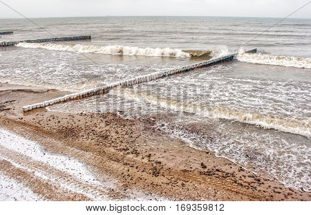 breakwater covered by ice breaking waves on cold gloomy winter day