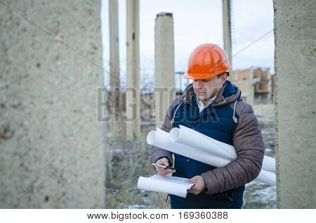 The man worker wear a orange helmet with drawings at the construction site