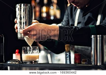 Closeup of bartender hands pouring alcoholic drink into a jigger to prepare a cocktail in a serving glass.