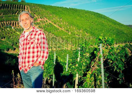winemaker standing by his vineyard, proud of his produce.