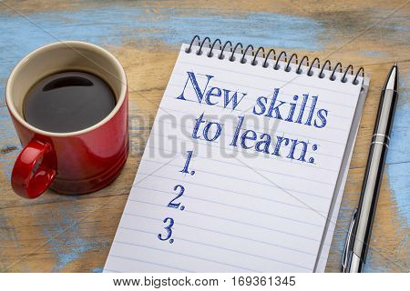 New skills to learn list in notebook a spiral notebook with a cup of coffee, goal setting and resolutions concept