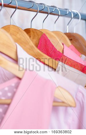 pink womens clothes on wood hangers on rack in a fashion store. . closet women dresses, blouses close up