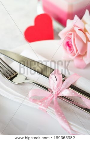 Valentines day table setting. Plate, silverware flower and gift box.