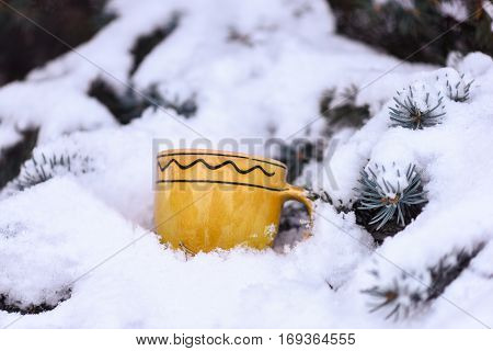 yellow ornamented with waves cup outdoor on snowy firry tree branches on natural background selective focus