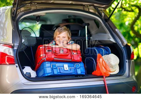 Adorable little kid boy sitting in car trunk just before leaving for summer vacation with his family. Happy child with suitcases and toys going on journey.