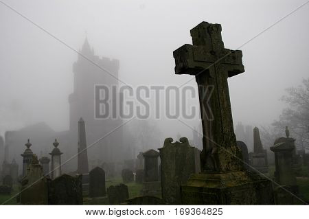 Spooky graveyard with cross in foreground and church outline in background