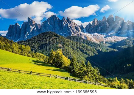 The bright morning sun illuminates rural picturesque farm and green alpine valley in the Dolomites. The concept of eco-tourism in Alpine meadows