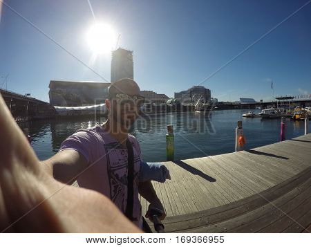 Man taking a selfie in Darling Harbour, Sydney, Australia