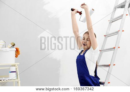 Young female decorator sitting on ladder in empty room