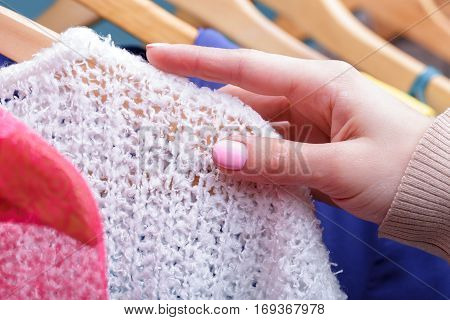 female hand selects new colorful clothes on wood hangers on rack in store, closeup. Shopping concept