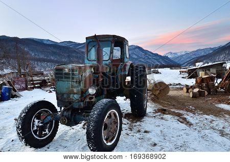 Caucasus Russia - Feb 18 2012: Old rusty soviet tractor shown on courtyard farmhouse in village in mountain region of Caucasus mountain at sunrise in winter time