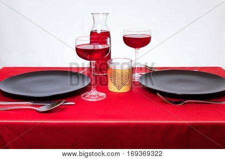 Elegant table setting in a restaurant on Valentine's Day. Wine and candle. Romantic dinner for two abstract concept.