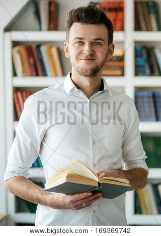 Young man in a white shirt standing with book in hand in the library. Many shelves with book on a blurred background