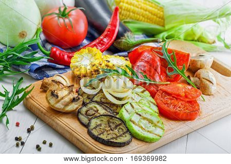Grilled vegetables meal and ingredients on a table. Tomato corn eggplant mushroom bell pepper marrow and onion prepared on a barbecue. Healthy food.