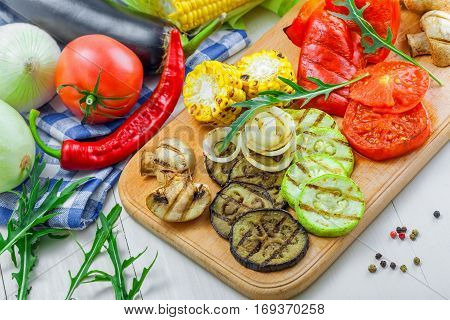 Grilled tomato corn eggplant mushroom bell pepper marrow and onion on a table. Healthy prepared food with ingredients.