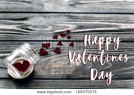 Happy Valentines Day Text Sign Concept. Stylish Velvet Hearts In Glass Jar On Black Rustic Wooden Ba