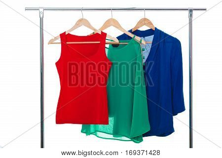 colorful women's shirts on wood hangers on rank on white background. RGB concept