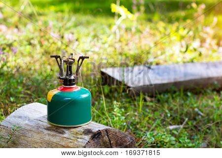 Touristic camping burner installed on gas cylinder tank in background of summer forest. Compact kitchen stove for cooking hot food in field travel conditions. Adventure Park