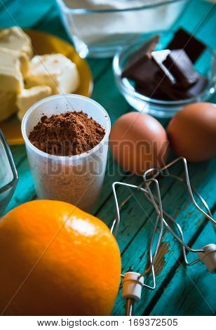 Close-up of grocery set to bakery with butter eggs flour chocolate cacao orange and sour cream.