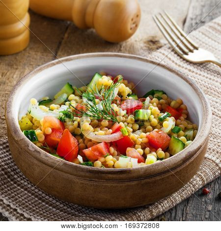 Traditional Israeli healthy meal Ptitim with tomatoes cucumber and onion for delicious healthy breakfast. Classic Moroccan couscous with vegetables.