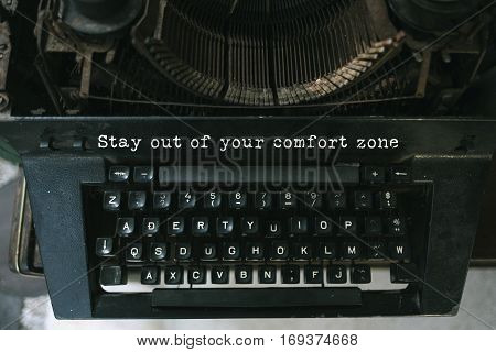Typewriter with white paper page on wooden table. sample text Stay out of your comfort zone.