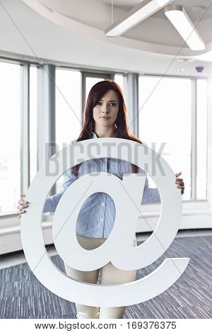 Portrait of beautiful businesswoman holding at sign in creative office