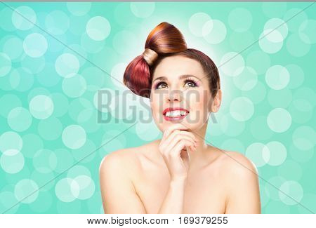 Beautiful smiling girl with a bow haircut and colorful make-up on bubble background.