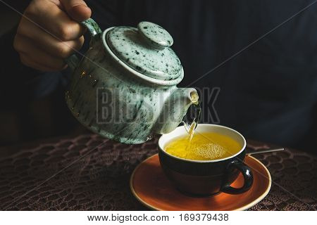 man pours tea from a teapot in a tea Cup. Close-up