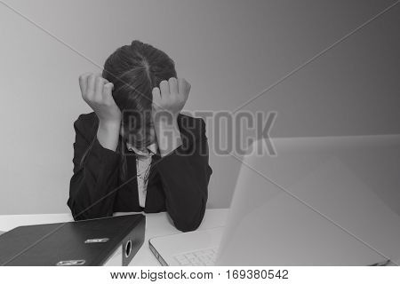 Stressed businesswoman hold her head with hands in the office with notebook and file - black and white concept