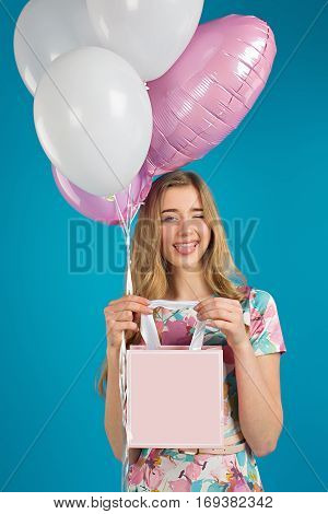 Sweet Nice Girl With Baloons And Little Prersents Bag In The Hands On The Blue Background.
