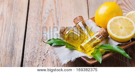 Health and beauty, still life concept. Organic essential lemon oil in a small glass jar with green leaves and yellow fruit on a rustic wooden table. Copy space background